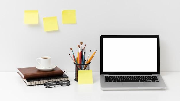 Arreglo de elementos de escritorio con laptop de pantalla vacía
