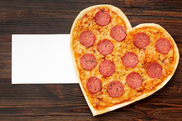 Arreglo encantador para la cena del día de san valentín con pizza en forma de corazón y tarjeta