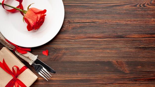 Arreglo encantador para la cena del día de san valentín sobre fondo de madera con espacio de copia