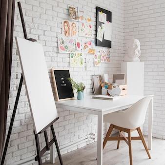 Arreglo con escritorio de artista y lienzo.