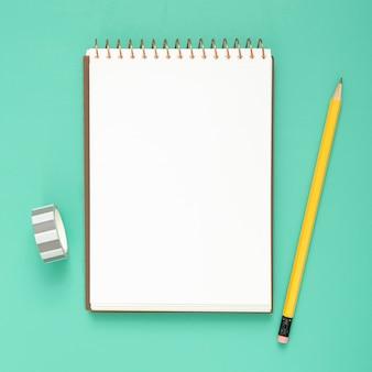 Arreglo de escritorio con bloc de notas vacío sobre fondo azul.