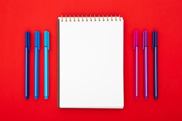 Arreglo de escritorio con bloc de notas vacío sobre fondo rojo.