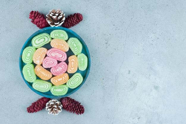 Arreglo festivo de piñas y bandeja de mermeladas sobre mármol.