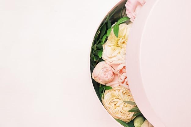 Un arreglo floral elegante y delicado en una caja redonda de sombrero sobre el fondo rosa con espacio de copia. caja de regalo para el 8 de marzo, día internacional de la mujer, día de la madre, día de san valentín, cumpleaños,