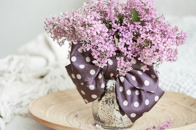 Arreglo floral con flores frescas de color lila y un lazo como detalle decorativo.