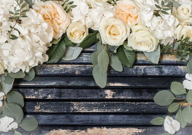 Arreglo floral de hermosas rosas blancas sobre fondo de madera, concepto de flores