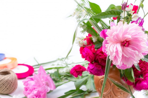 Arreglo floral con un hermoso ramo de flores de peonía rosa, acianos y rosas rojas.
