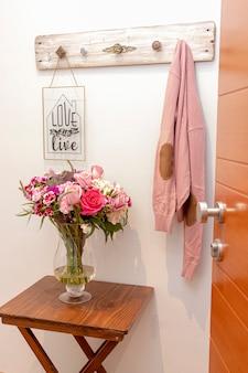 Arreglo floral de rosas y hortensias en la entrada de la casa.