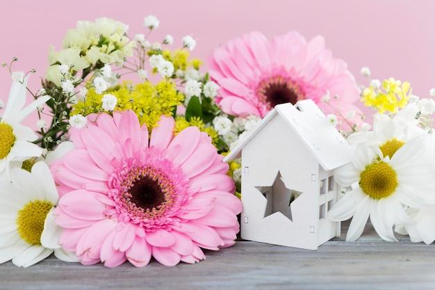 Arreglo con flores y casa de madera.