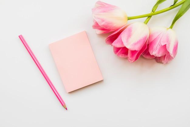 Arreglo de flores y cuaderno con lapiz.