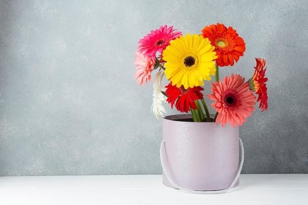 Arreglo de flores de gerbera margarita en un cubo