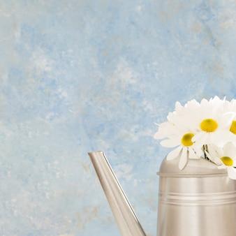 Arreglo con flores en una regadera