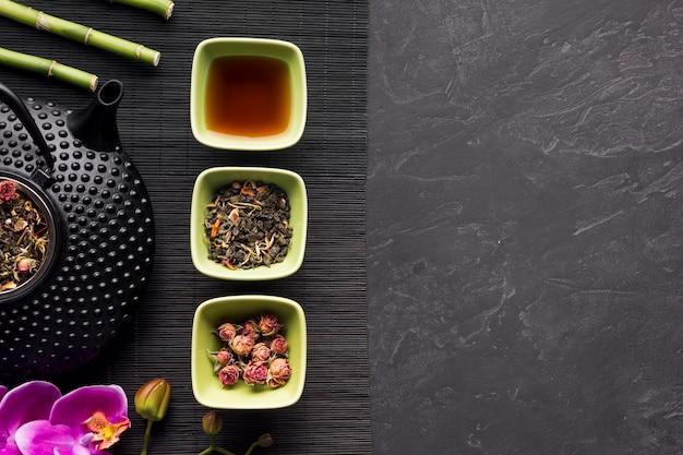 Arreglo de flores secas y hierbas de té en mantel negro sobre fondo