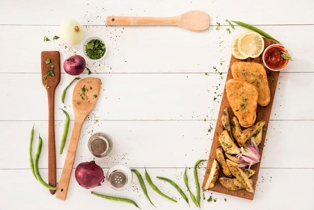 Arreglo de la frontera de los utensilios de cocina y comida preparada en el escritorio de madera