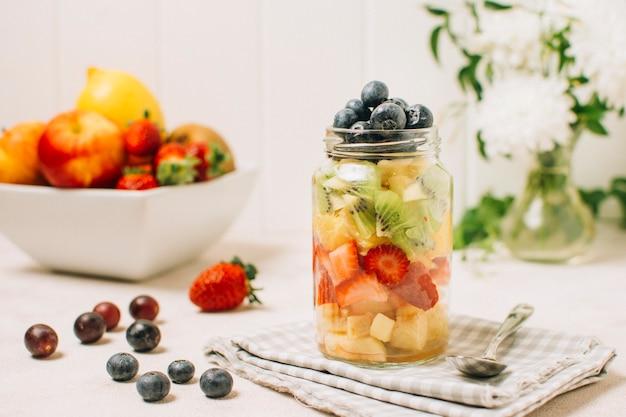 Arreglo de frutas coloridas en un tarro.