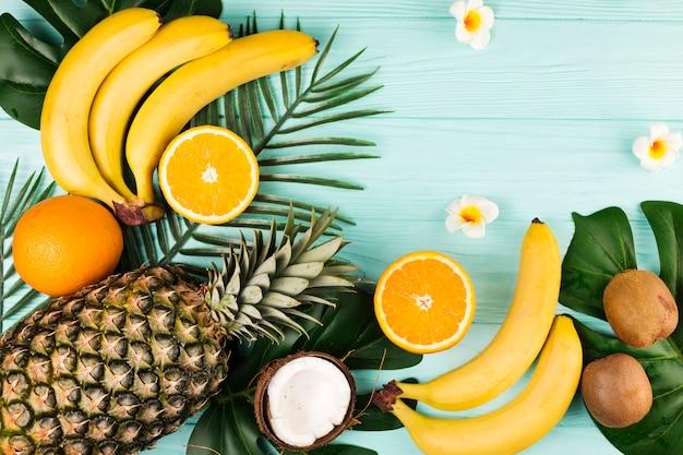 Arreglo de frutas y hojas tropicales.
