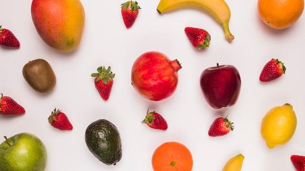 Arreglo de frutas tropicales sobre superficie blanca.