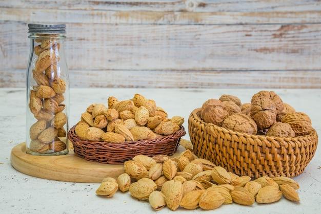 Arreglo de frutos secos, almendras y nueces en rústica mesa de madera vieja