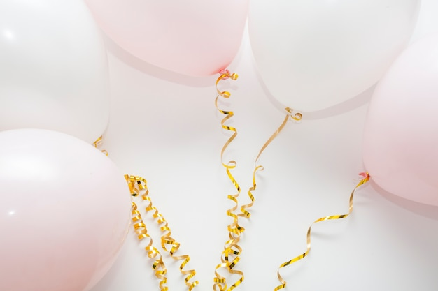 Arreglo de globos con cintas doradas.