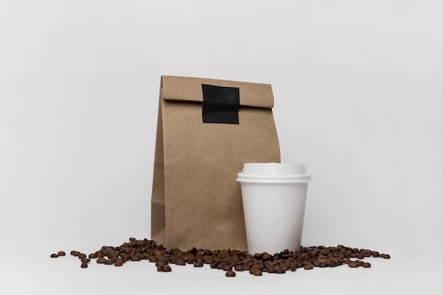 Arreglo de granos de café y bolsas de papel