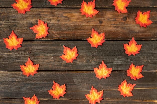 Arreglo de hojas de naranja sobre fondo de madera