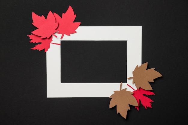 Arreglo de hojas de otoño de papel en marco blanco