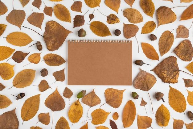Arreglo con hojas secas y cuaderno de manualidades