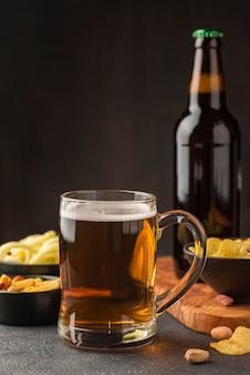 Arreglo con jarra de cerveza y snacks.