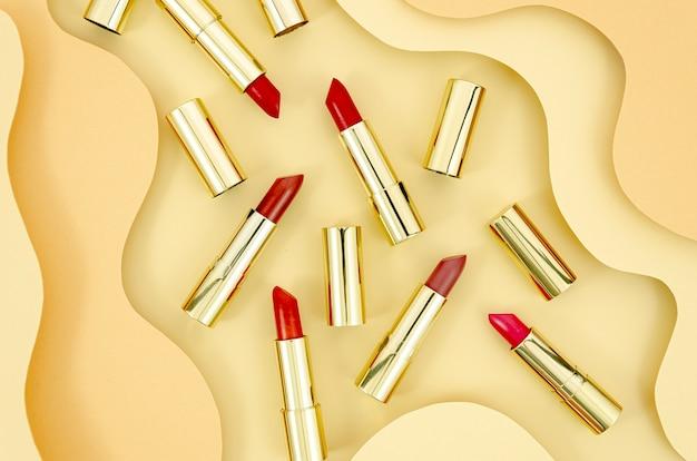 Arreglo de lápices labiales coloridos con fondo abstracto