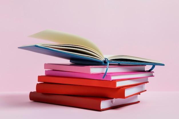 Arreglo con libros y fondo rosa.
