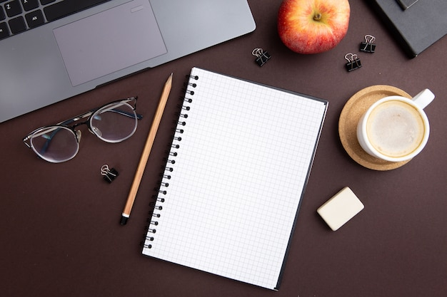Arreglo de lugar de trabajo moderno con cuaderno vacío
