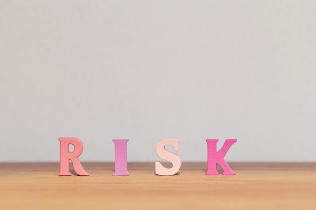 Arreglo de madera letras palabra riesgo en la mesa