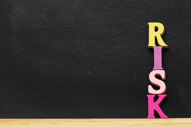 Arreglo de madera letras palabra riesgo en pizarra