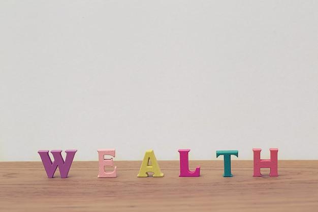 Arreglo madera letras palabra riqueza en mesa