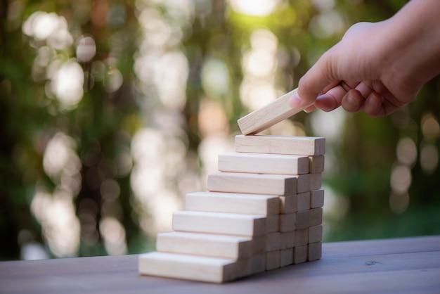 Arreglo de mano apilamiento de bloques de madera como paso sobre fondo roto