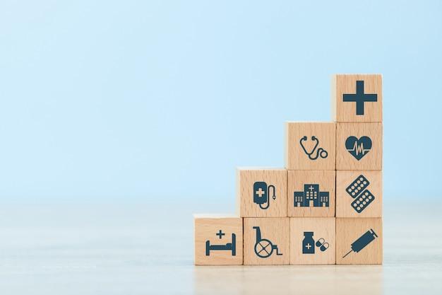 Arreglo de mano apilar bloque de madera con el icono de salud médica.