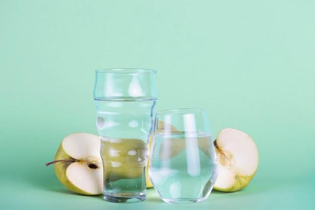 Arreglo de manzanas verdes y vasos de diferentes tamaños