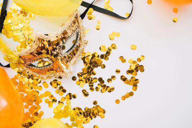 Arreglo de máscara dorada y confeti.