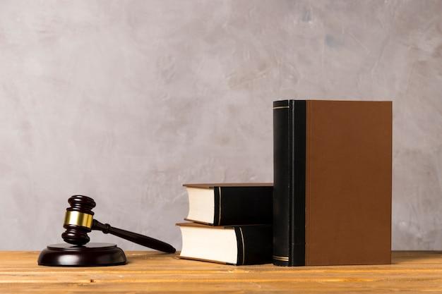 Arreglo con mazo de juez, bloque llamativo y libros.