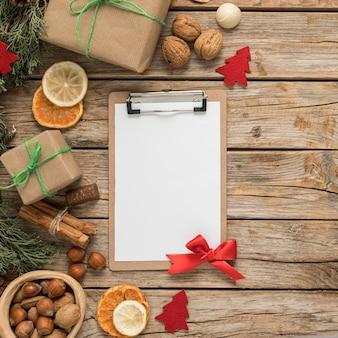 Arreglo de mesa de navidad festiva endecha plana con portapapeles vacío