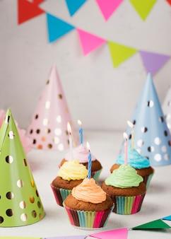 Arreglo con muffins, velas y sombreros de fiesta.
