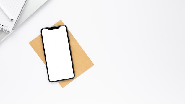 Arreglo de negocios creativos sobre fondo blanco con teléfono con pantalla vacía