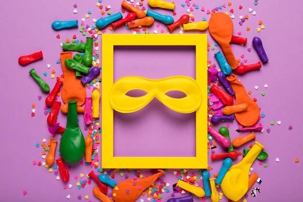 Arreglo de objetos de carnaval con marco amarillo.
