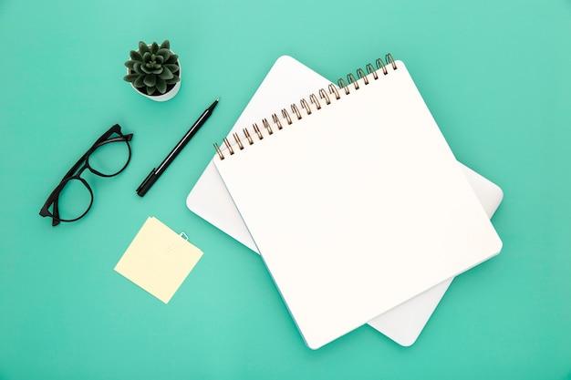 Arreglo organizado de elementos de escritorio sobre fondo verde