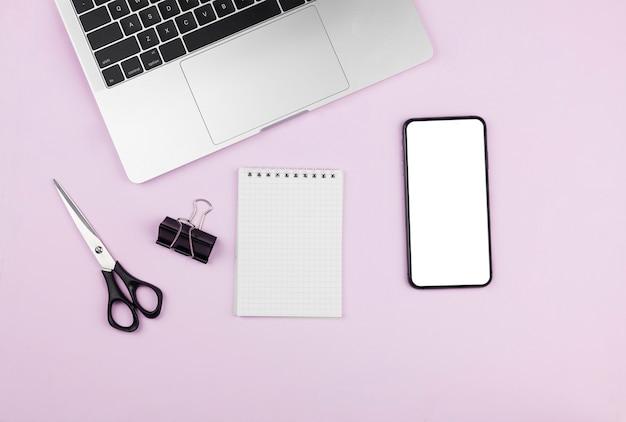 Arreglo de papelería con bloc de notas y maqueta de teléfono