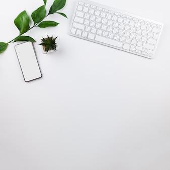 Arreglo de papelería sobre fondo blanco con maqueta de teléfono