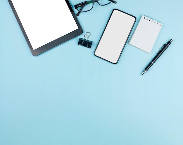 Arreglo de papelería con tableta y maqueta de teléfono