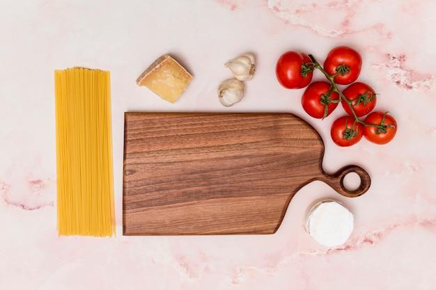 Arreglo de pasta cruda e ingrediente sabroso y tabla de cortar de madera en superficie de mármol