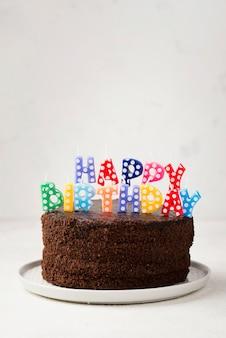 Arreglo con pastel de cumpleaños y velas.