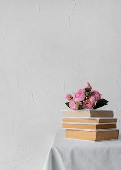 Arreglo con pila de libros y flores.